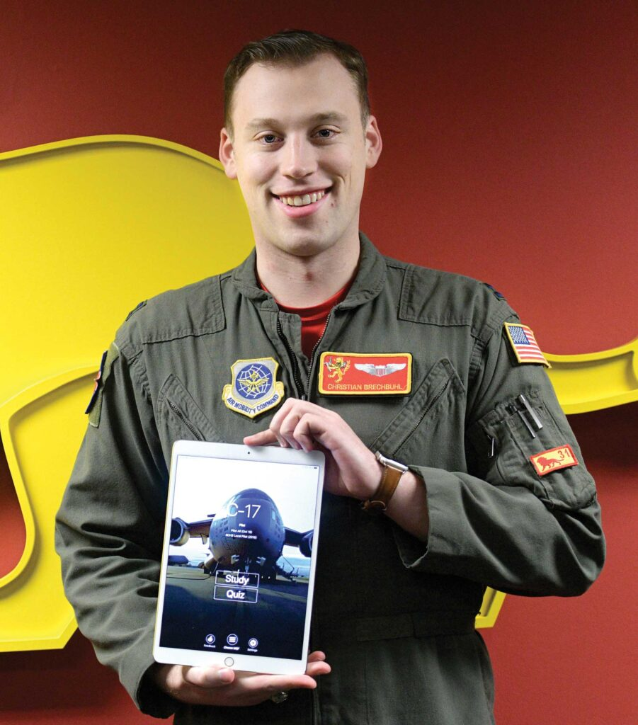 Capt Christian Brechbuhl, an Assistant Flight Commander assigned to the 16th Airlift Squadron, holds up a mobile device displaying an application he developed to help aircrews study for annual certifications at Joint Base Charleston, SC, Feb. 7, 2020. The application was developed cost-effectively by Airmen from multiple bases who volunteered their time to write the code. It centralizes necessary study material for aircrew annual certification and is currently being utilized by three airframes throughout Mobility Air Forces. USAF photo by SrA Joshua R. Maund