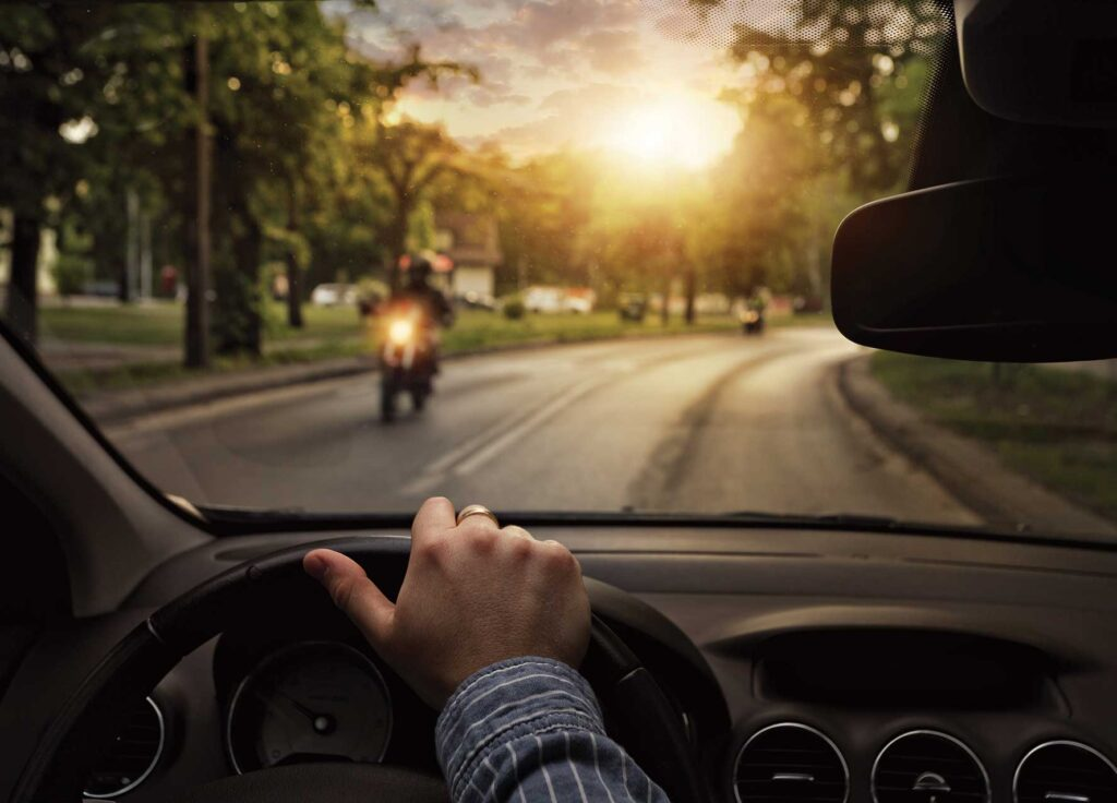 Looking over the steering wheel, a driver sees two motorcyclers ahead.
