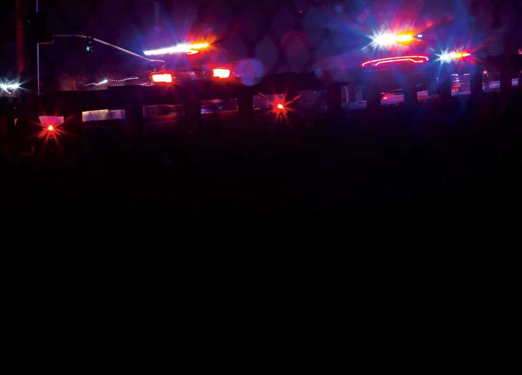 Red and white lights of police vehicles reflect through a dark haze.